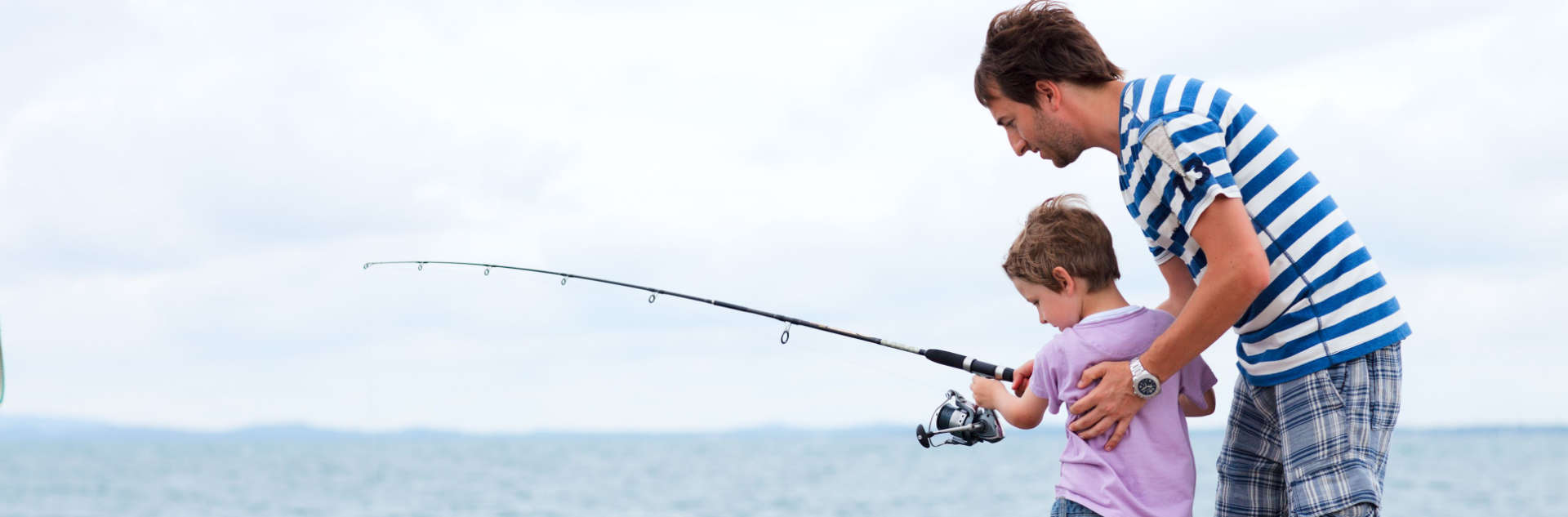 father and son while fishing at the sea