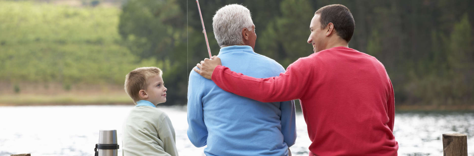 a photo of three people, son, father and grandfather while fishing at a lake