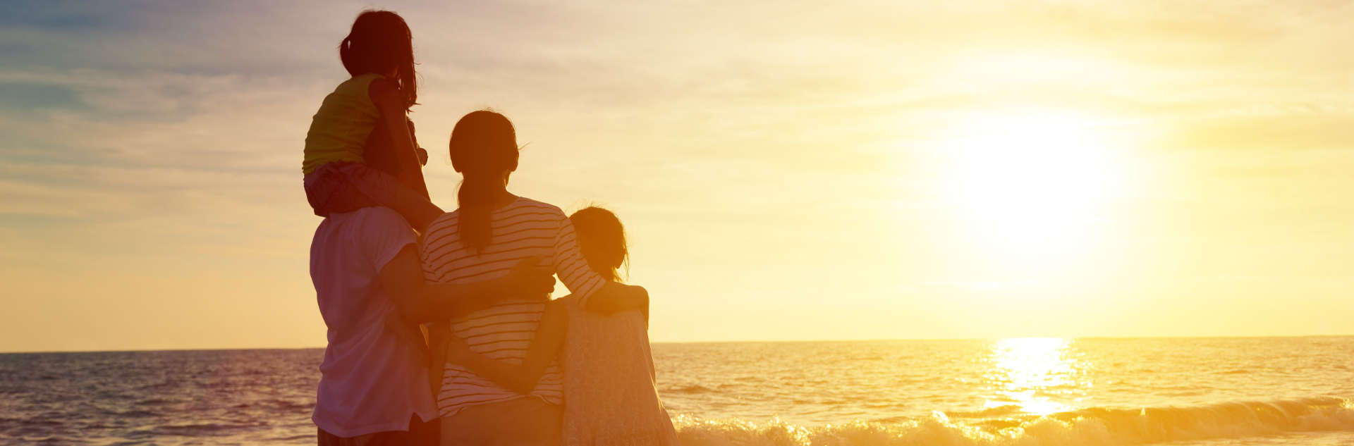 couple and their two children watching the sunset at the beach