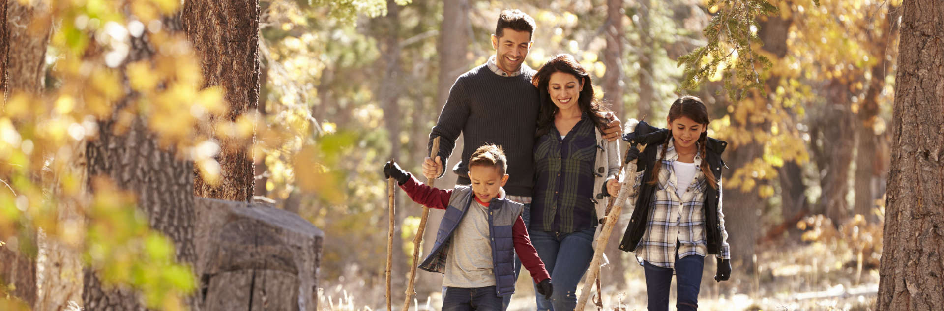 a couple with their two children walking in the woods