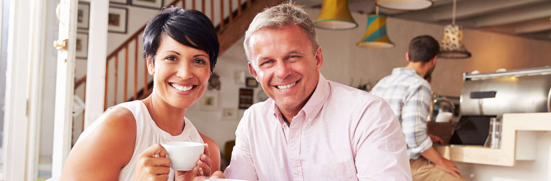 couple smiling to the camera while drinking tea in a coffee house