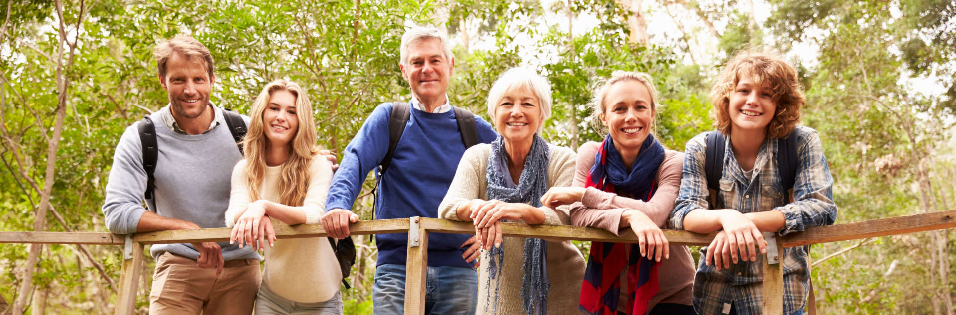 family of 6 smiling to the camera while standing on a bridge