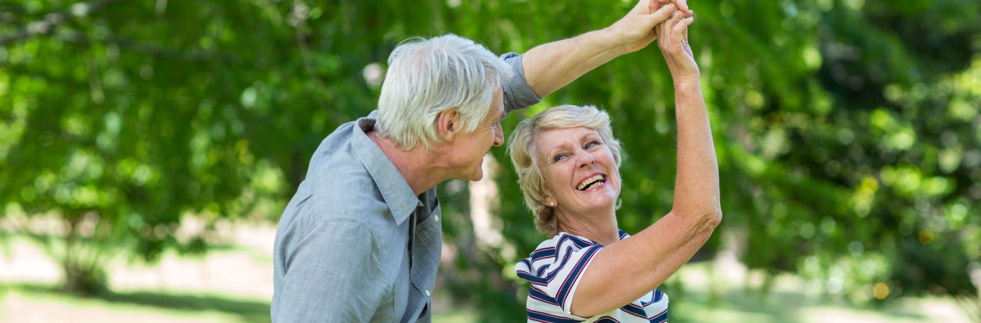 older happy couple dancing in the park