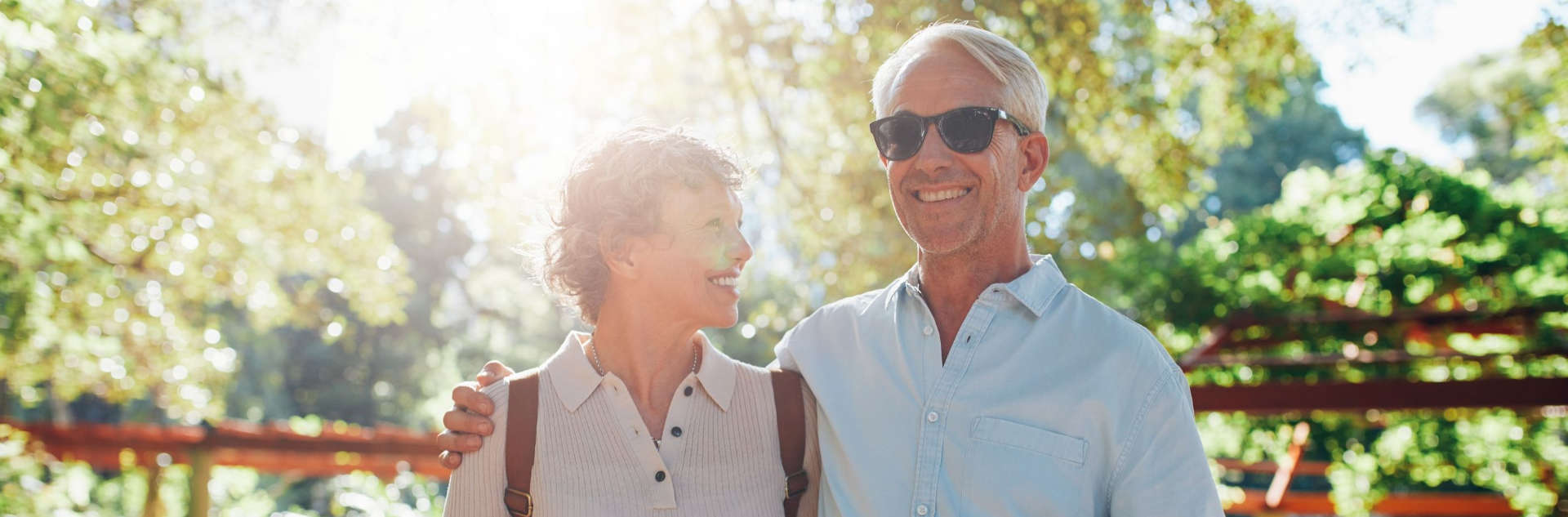 older couple smilign to the camera while outdoors