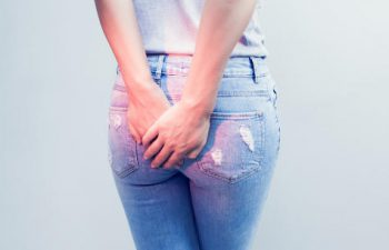 Woman hand holding her bottom because having Abdominal pain and Hemorrhoids