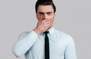Embarrassed man covering his mouth with his hand